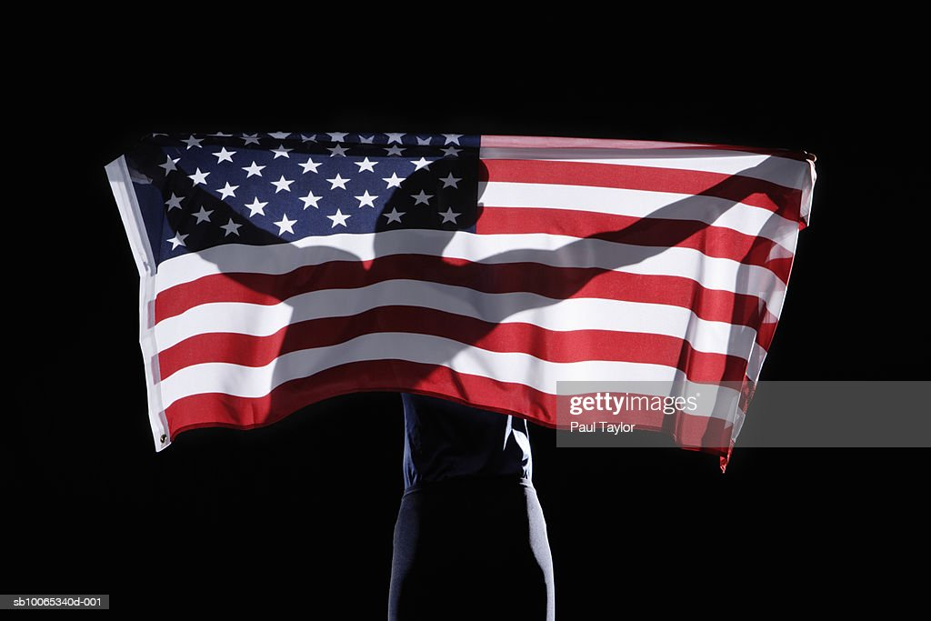 Silhouette of person holding flag of USA on black background : Foto stock