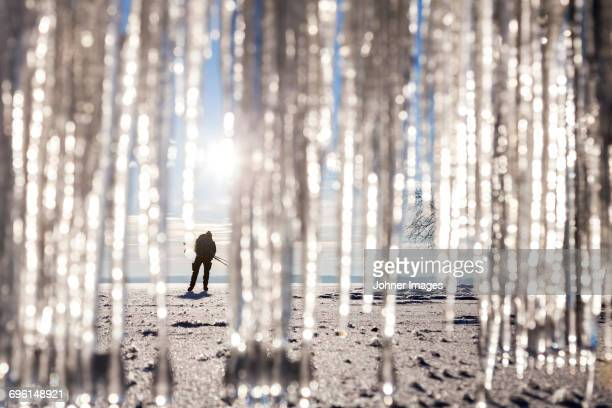 silhouette of person on beach. icicles on foreground - norrkoping fotografías e imágenes de stock