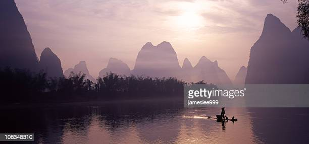 Silhouette of person on boat floating on Lijiang River