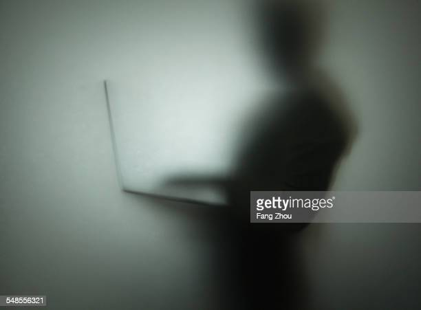 silhouette of person using laptop, behind glass - private stock pictures, royalty-free photos & images