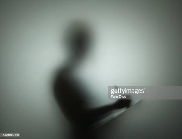 Silhouette of person using pen and clipboard, behind glass