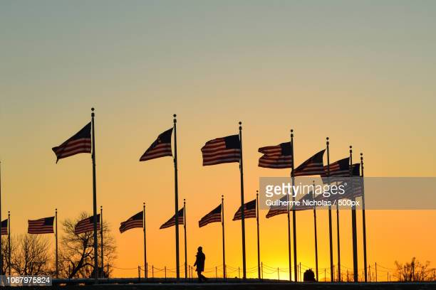 silhouette of person walking by circle of flagpoles with american flags at sunset - flagpole sitting stock photos and pictures