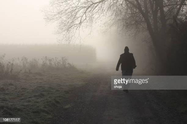Silhouette von Menschen zu Fuß im Nebel-Schotterstrecke