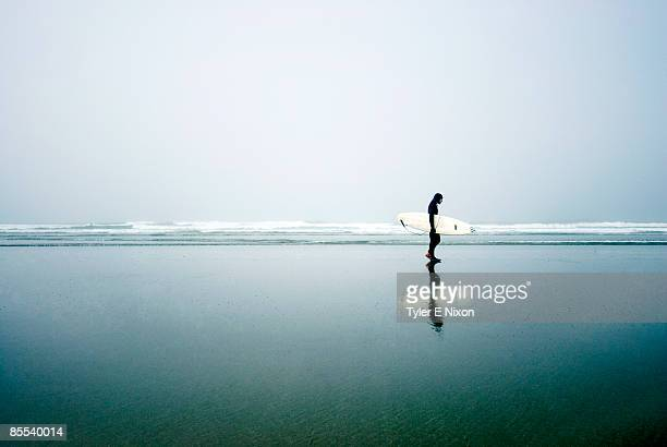 Silhouette of person walking on beach with surfboard