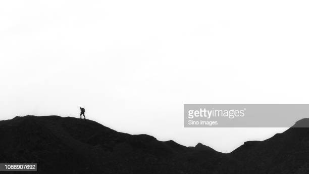silhouette of person walking on hills, xinjiang uygur autonomous region, china - image stock pictures, royalty-free photos & images
