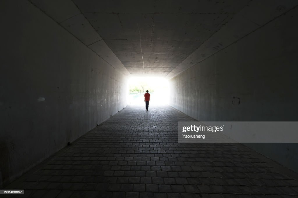 silhouette of person walking out of  a tunnel. Light at End of Tunnel : Stock Photo