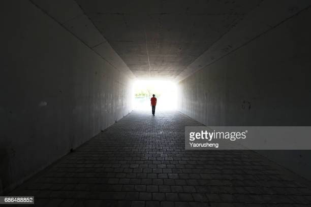 silhouette of person walking out of  a tunnel. light at end of tunnel - tod stock-fotos und bilder