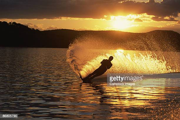 silhouette of person waterskiing - waterskiing stock photos and pictures