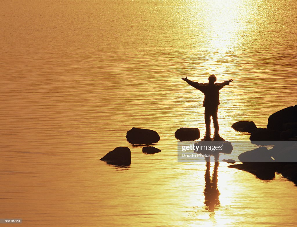 silhouette of person with outstretched arms on rocks at beach stock