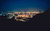 Silhouette of photographer standing on mountain top against illuminated cityscape and taking photos of the night scene