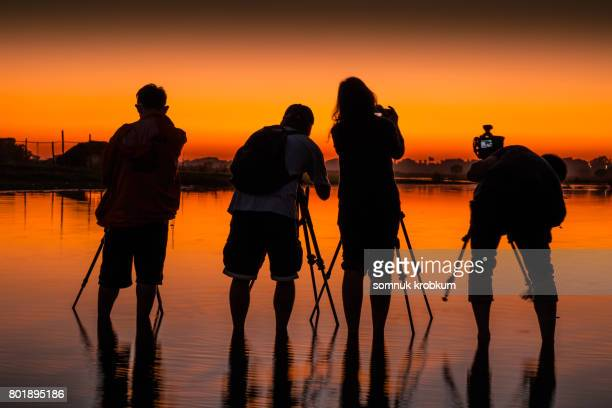 Silhouette of Photographers are working after sunset in shallow riverbank around U Bein Bridge ; Myanmar