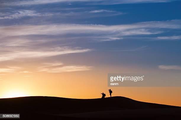 Silhouette of photographers in desert Sahara on sunset, Morocco