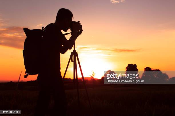 silhouette of photography with a sunset setting - rahmad himawan stock pictures, royalty-free photos & images