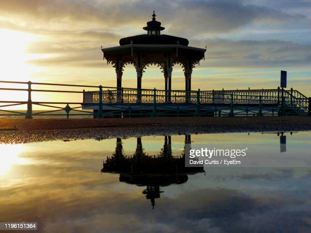 silhouette of pier on sea during sunset - brighton stock pictures, royalty-free photos & images