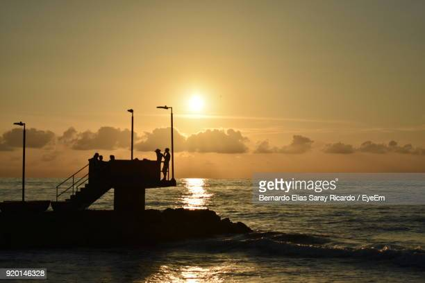 Silhouette Of Pier On Sea During Sunset
