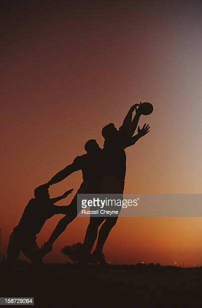 Silhouette of players reaching for the ball on 2nd December 1990 during the Dubai Rugby Sevens tournament at the Dubai Exiles Rugby Ground in Dubai