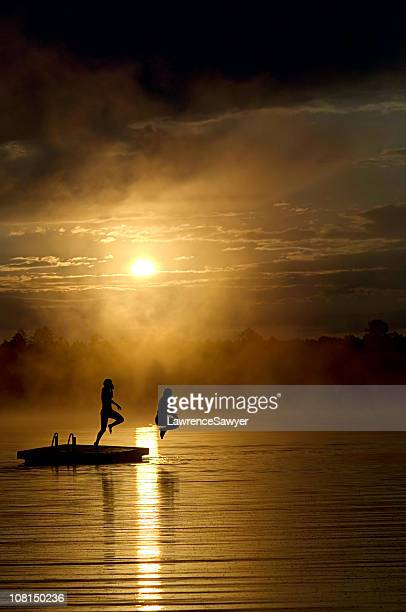 Silhouette of Poeple Jumping off Dock at Sunset