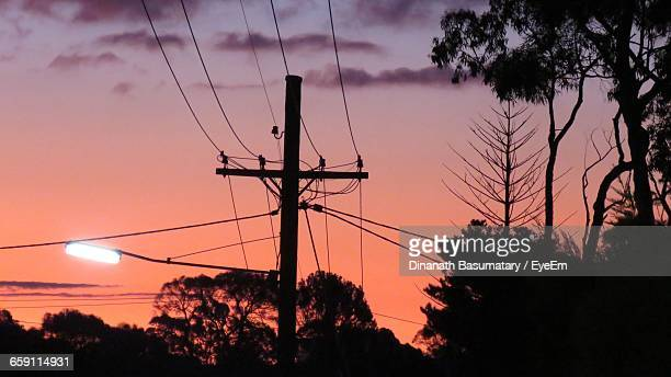 Silhouette Of Power Lines And Trees Against Dramatic Sky