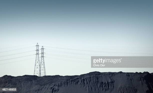 Silhouette of power lines over rocky landscape