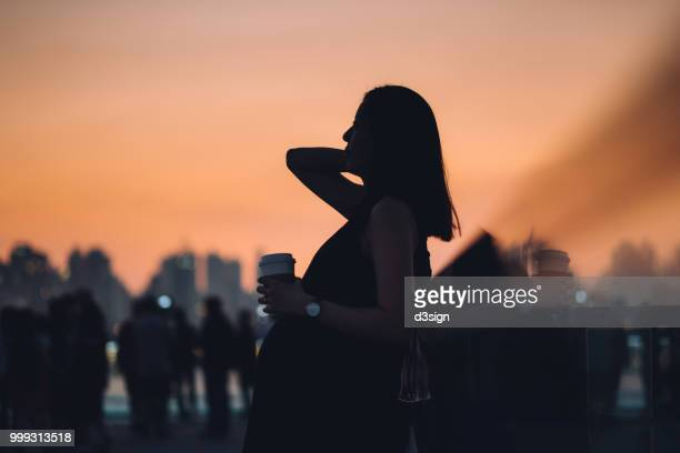 Silhouette of pregnant woman having a cup of coffee and enjoying the beautiful sunset in city