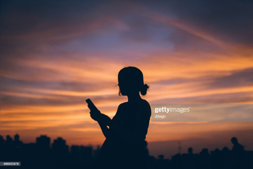 Silhouette of pregnant woman using mobile phone against dramatic sky during sunset : Stock Photo