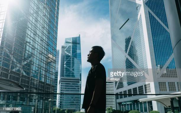silhouette of professional young businessman standing against contemporary financial skyscrapers and looking up into sky with positive emotion - central district hong kong stock pictures, royalty-free photos & images