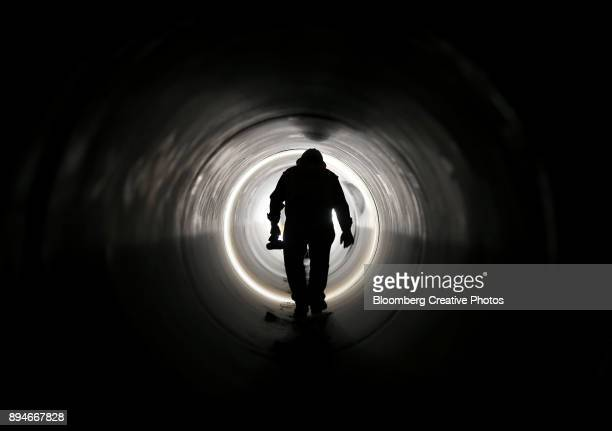A silhouette of project manager is seen as he walks in a 60 inch pipe at a reservoir