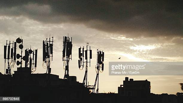 Silhouette Of Repeater Towers On Building During Sunset