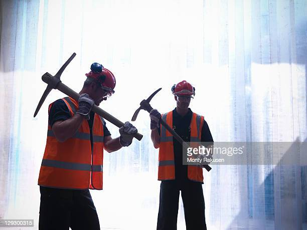 Silhouette of road workers holding pickaxes