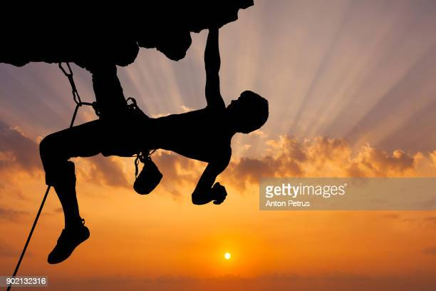 Silhouette of rock climber climbing an overhanging cliff with sunset