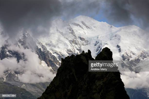 silhouette of rock formation against the mont blanc massif, chamonic valley and mont blanc summit, peak with dark clouds and blue sky - pinnacle peak stock pictures, royalty-free photos & images