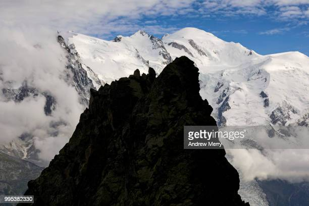 silhouette of rock formation against the mont blanc massif, chamonic valley and mont blanc summit, peak with clouds and blue sky - pinnacle peak stock pictures, royalty-free photos & images