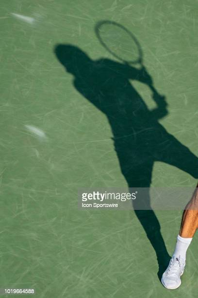 A silhouette of Roger Federer of Sweden returning the ball to Novak Djokovic of Serbia during the men's final on Day 8 of the Western and Southern...