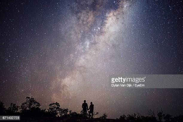 Silhouette Of Romantic Couple Under Star Field Sky