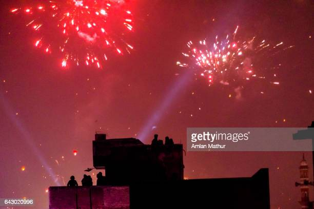 Silhouette of rooftop over fireworks