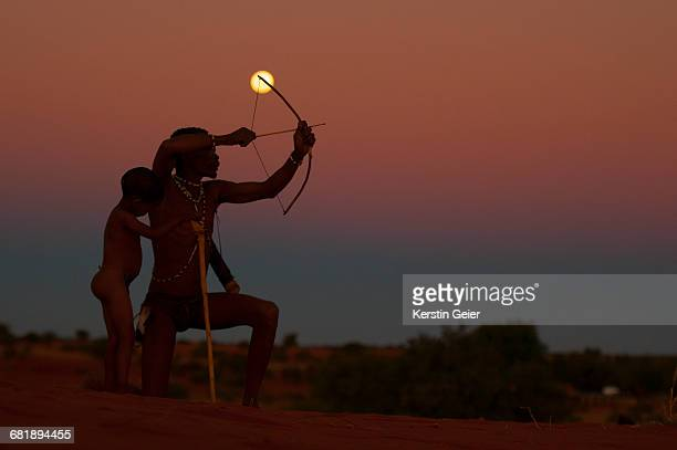 Silhouette of San (Bushmen) on top of dunes at full moon. Stampriet District, Namibia.