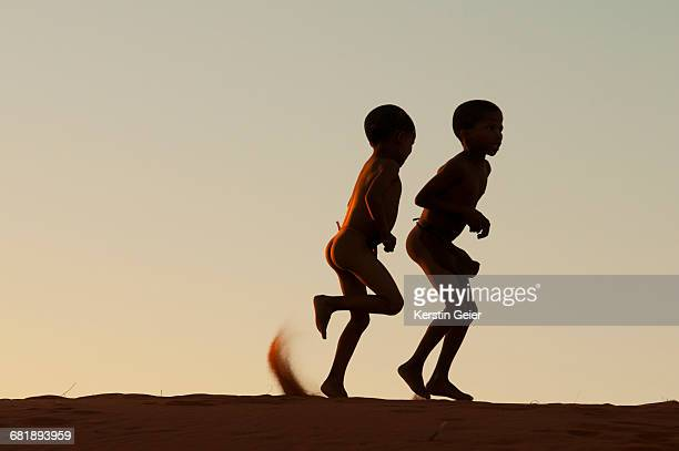 Silhouette of San (Bushmen) on top of dunes at sunset. Stampriet District, Namibia.