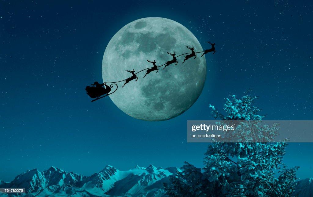Silhouette of Santa and reindeer flying sleigh near full moon : ストックフォト