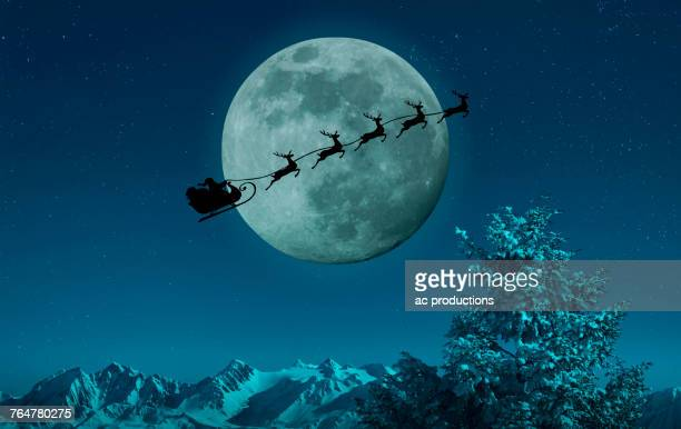 silhouette of santa and reindeer flying sleigh near full moon - santa claus fotografías e imágenes de stock