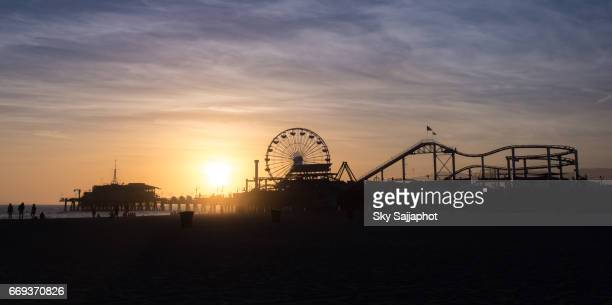 Silhouette of Santa Monica Pier sunset with cloud and blue sky, Los Angeles, USA
