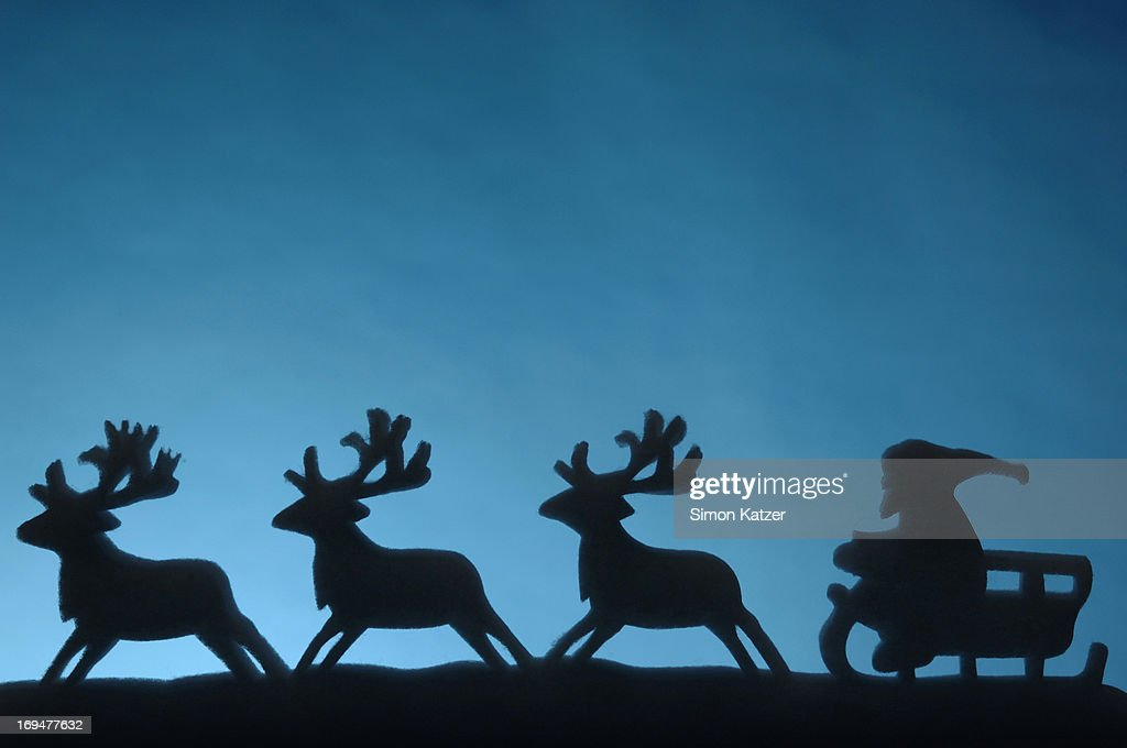 Silhouette of Santa with his reindeers : Stock Photo