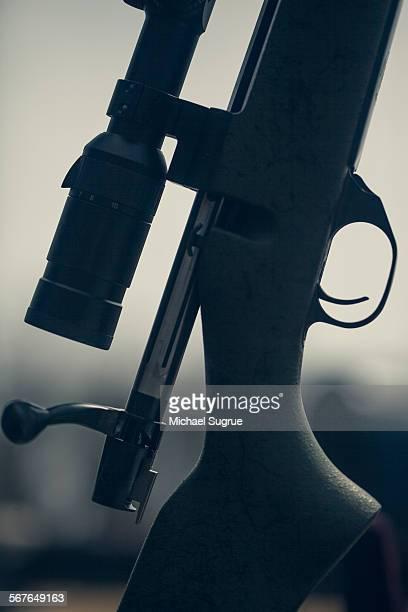 Silhouette of scope rifle on target range.