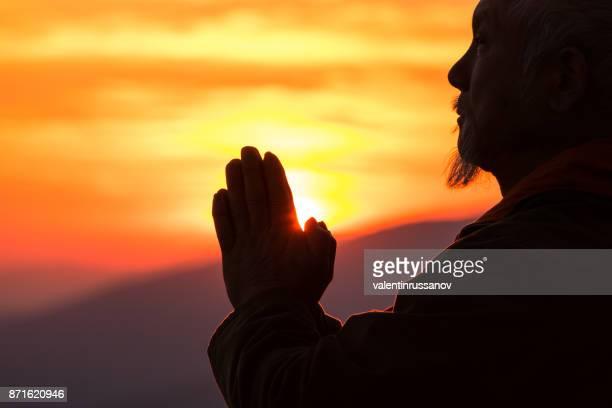 Silhouette of senior asian man praying on top mountain