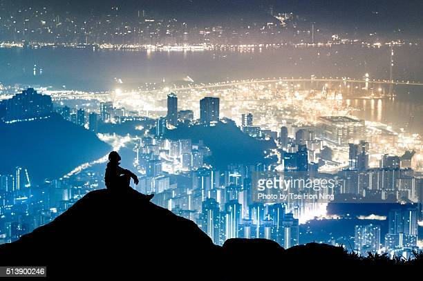 silhouette of sitting hiker with hong kong city urban night view