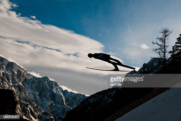 Silhouette of ski jumper in mid-air