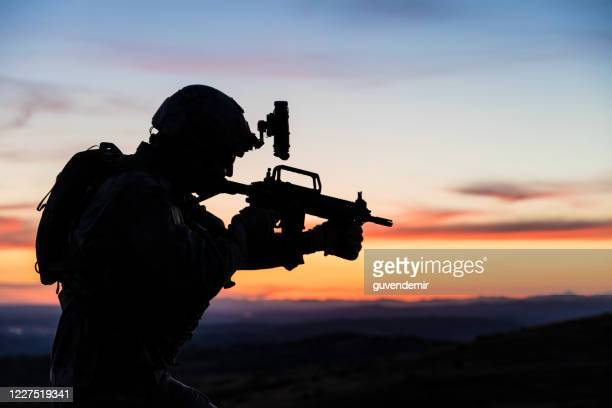 silhouette of soldier during military mission at sunset - army soldier stock pictures, royalty-free photos & images