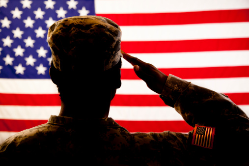Silhouette of soldier saluting the American flag 496685059