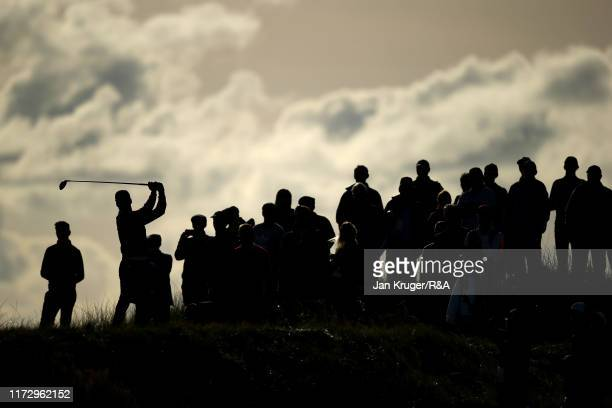 Silhouette of spectators and Isaiah Salinda of the United States as he tees off on the fourteenth in the singles matches during Day 1 of the Walker...