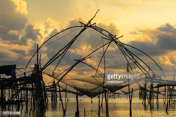 Silhouette of square dip nets with sunrise sky background, livelihoods of fishermen at Pakpra, Phattalung in Thailand