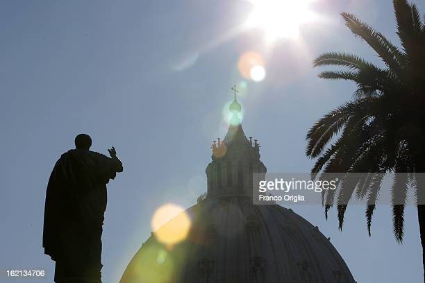 A silhouette of St Peter's statue in front of St Peter's Basilica is seen from the Vatican Gardens on February 19 2013 in Vatican City Vatican When...